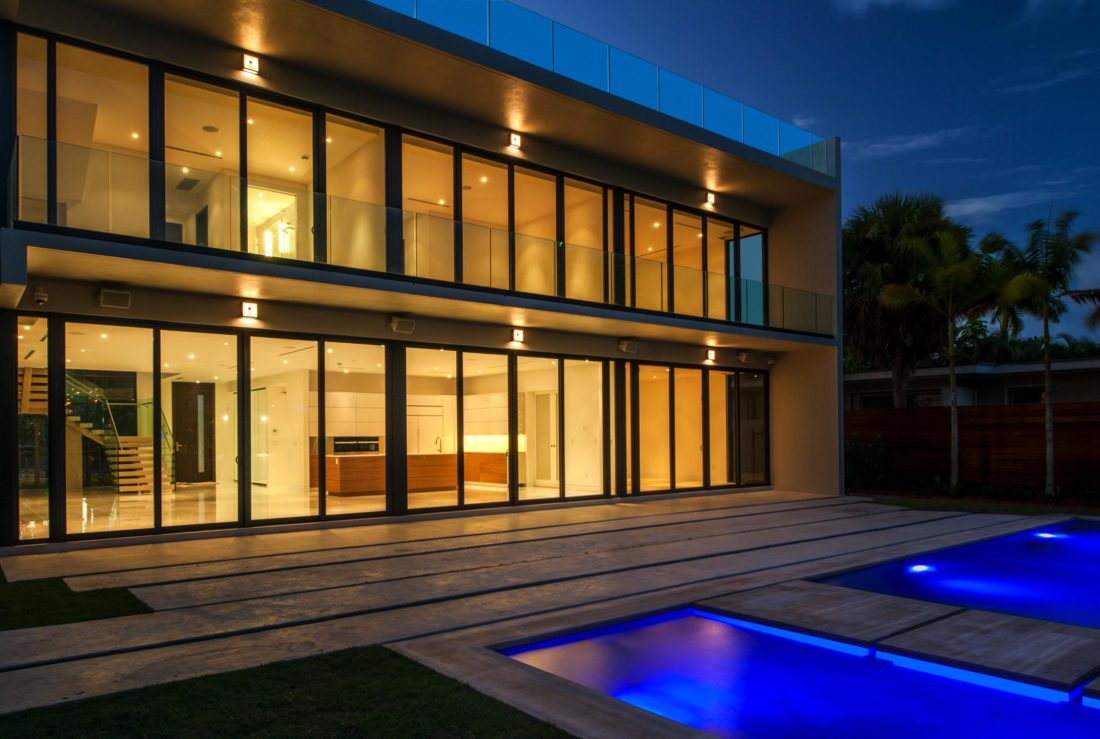 Floor to ceiling windows showcase the backyard and water views