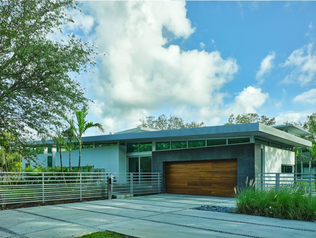 Stained wood garage and steel fencing enhances the front of the home